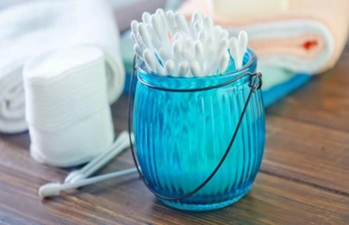 Cotonetes num pote azul, com três cotonetes ao lado, com toalhas ao fundo em uma superfície de madeira