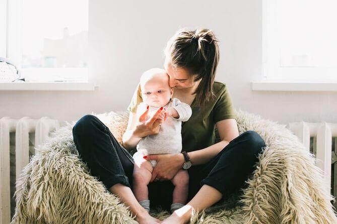 Mãe com bebê no colo.